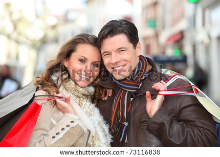 Happy couple doing shopping in town