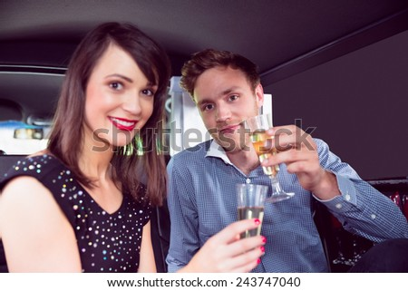 Happy couple drinking champagne in limousine on a night out - stock photo