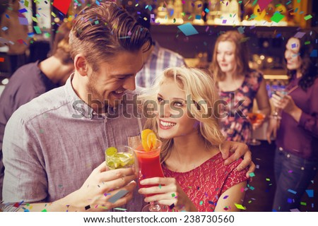 Happy couple drinking cocktails together against flying colours - stock photo