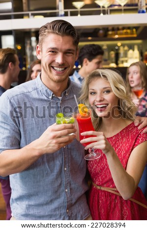 Happy couple drinking cocktails together at the bar - stock photo
