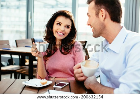 Happy couple drinking coffee and talking in a canteen - stock photo