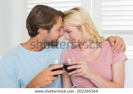 Happy couple drinking red wine together on the couch at home in the living room - stock photo