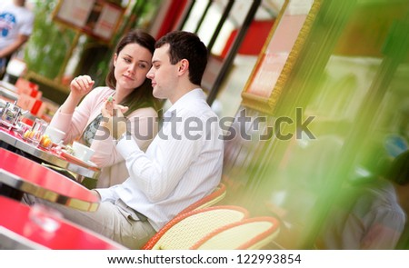 Happy couple eating delicious macaroons in a Parisian outdoor cafe - stock photo