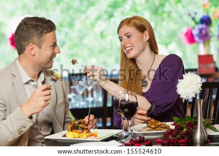 Happy couple eating together in a classy restaurant