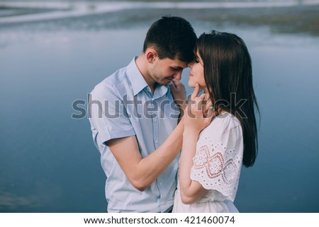 Happy couple embraced, in the lake background
