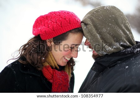 Happy couple embracing and having fun wearing warm clothes outside