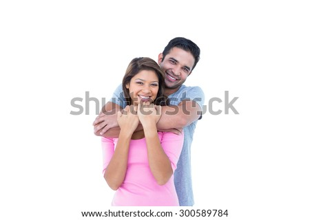 Happy couple embracing and looking at the camera on white background - stock photo