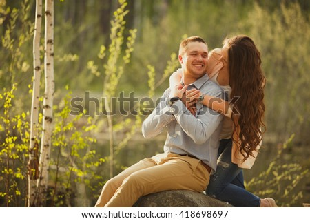 Happy couple embracing at sunset in the nature. young couple hugging at sunset elegantly dressed businessmen. Family values, adult life.