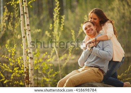 Happy couple embracing at sunset in the nature. young couple hugging at sunset elegantly dressed businessmen. Family values, adult life. - stock photo