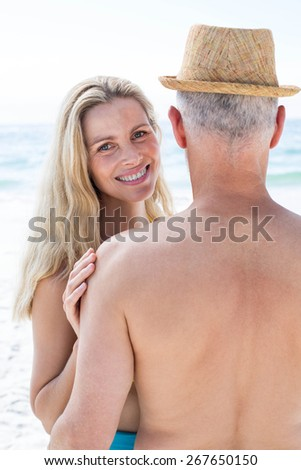 Happy couple embracing by the sea at the beach - stock photo