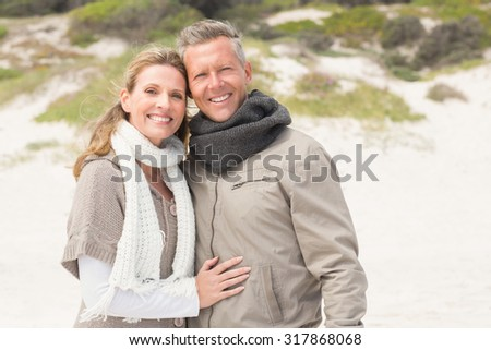 Happy couple embracing by the shore at the beach - stock photo