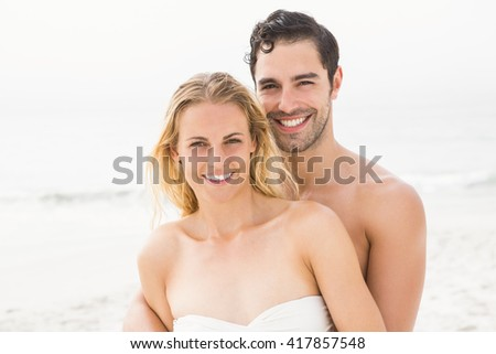 Happy couple embracing on the beach on a sunny day