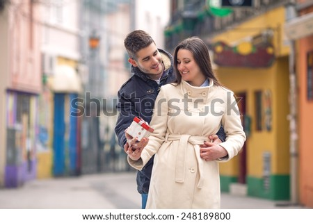 Happy couple embracing outdoors and exchanging gifts on Valentine's Day. - stock photo