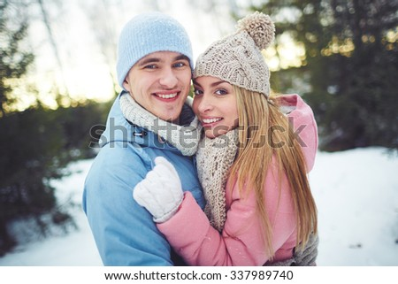 Happy couple embracing outdoors in winter - stock photo