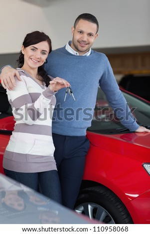 Happy couple embracing while holding keys in a car shop