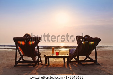 happy couple enjoy sunset on the beach - stock photo