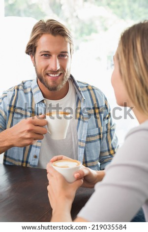 Happy couple enjoying a coffee at the coffee shop - stock photo