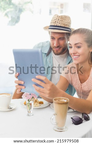 Happy couple enjoying coffee using tablet at the coffee shop - stock photo
