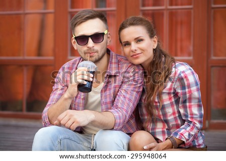Happy couple enjoying in European country. Man in sunglasses drinking cold Coca-Cola and sitting near by his girl-friend. - stock photo