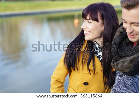 Happy couple enjoying nature while out on a date standing close together alongside a canal or lake, focus to the smiling young woman - stock photo