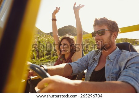 Happy couple enjoying on a long drive in a car. Friends going on road trip on summer day. Caucasian young man driving a car and joyful woman with her arms raised. - stock photo