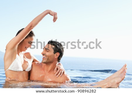 Happy couple enjoying their time together in the pool - stock photo