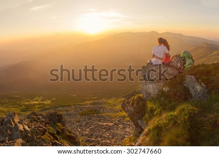 Happy couple feel freedom and enjoy the beautiful view in the mountains and looking on sunset - stock photo