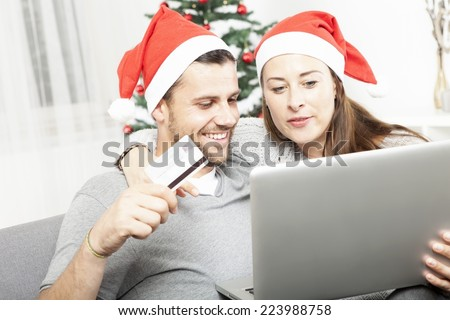 happy couple find perfect present gifts online on sofa indoors using credit card and laptop