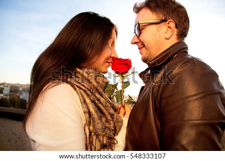 Happy couple for Valentine's Day. Loving couple enjoying the sun on the roof and beautiful girl smells a red rose, symbol of love. Affectionate Couple with red rose on the rooftop.