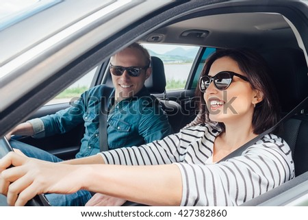 Happy couple goes by the car - stock photo
