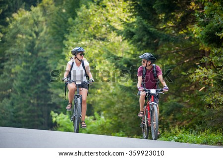 happy couple goes on a mountain asphalt road in the woods on bikes with helmets