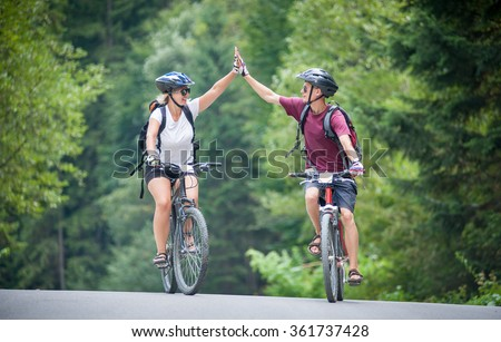 happy couple goes on a mountain asphalt road in the woods on bikes with helmets giving each other a high five - stock photo