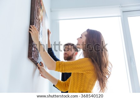 Happy couple hanging picture on the wall at home - stock photo