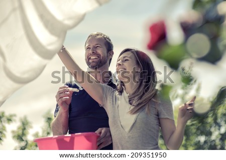 Happy couple hanging up laundry - stock photo
