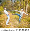 Happy couple have a fun in fall forest - stock photo