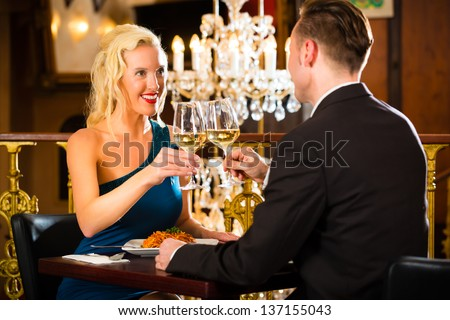 happy couple have a romantic date in a fine dining restaurant they drink wine and clinking glasses, cheers - a large chandelier is in Background