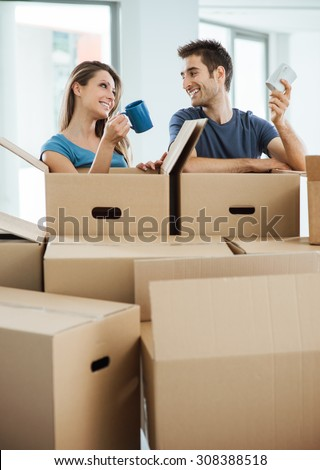 Happy couple having a coffee break during a relocation in their new house, they are holding a mug and smiling at each other - stock photo