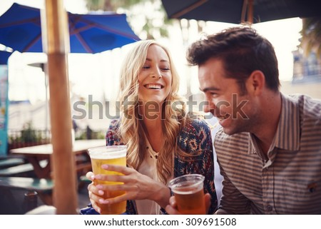 happy couple having a good time drinking beer together at outdoor pub or bar - stock photo