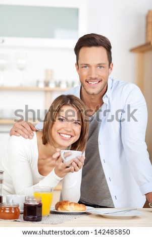Happy couple having breakfast in their kitchen - stock photo