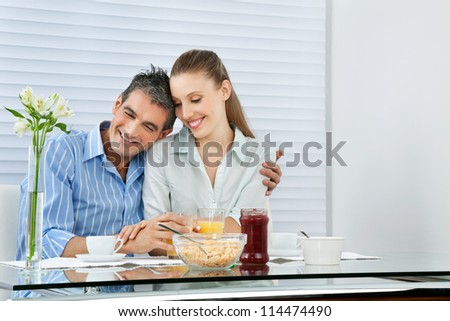 Happy couple having breakfast together at the table
