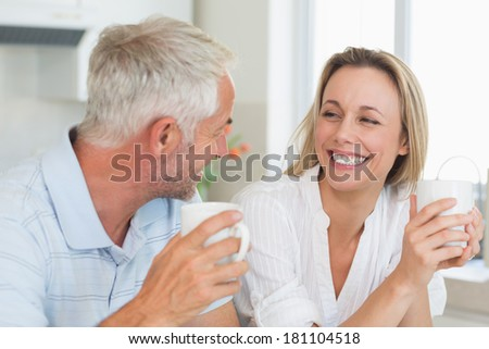 Happy couple having coffee together at home in the kitchen