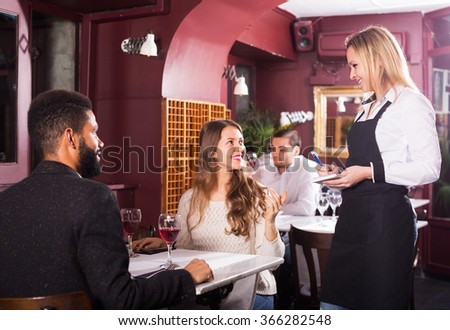 Happy couple having date in middle class restaurant. Focus on blonde girl - stock photo