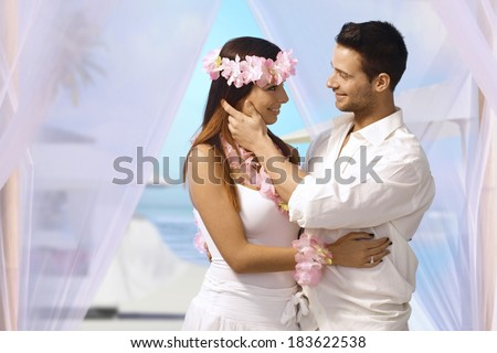 Happy couple having dream wedding on tropical island, embracing, caressing each other. - stock photo