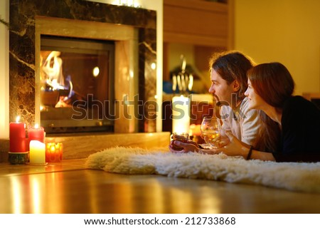 Happy couple having drinks by a fireplace in a cozy dark living room on Christmas eve - stock photo