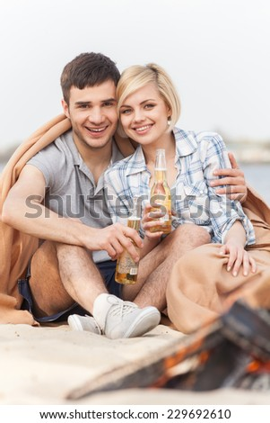 happy couple having fun around bonfire. two friends sitting under blanket and warming near fire - stock photo