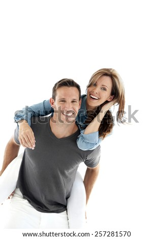 Happy couple having fun - Man giving piggyback ride to woman - isolated on white - stock photo