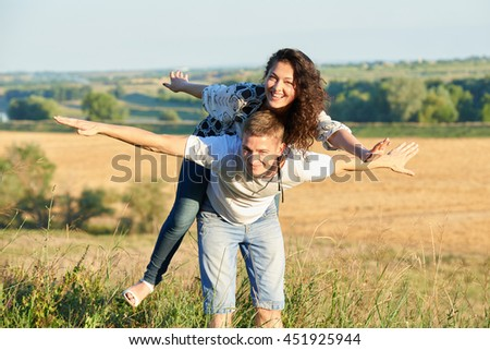 happy couple having fun on outdoor, girl riding on his back and fly - romantic travel, hiking, tourism and people concept - stock photo
