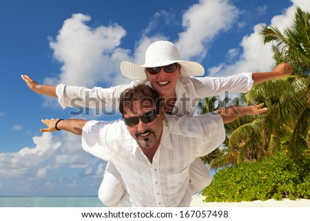 Happy Couple having fun on the beach  - stock photo