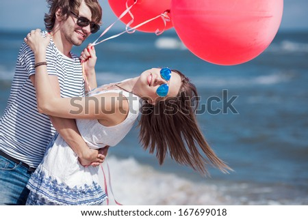 happy couple having fun on the beach, girl with open hands and red balloons, conception of freedom  - stock photo