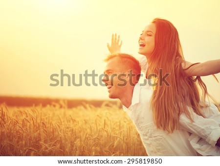 Happy Couple Having Fun Outdoors on wheat field over sunset. Laughing Joyful Family together. Freedom Concept. Piggyback - stock photo
